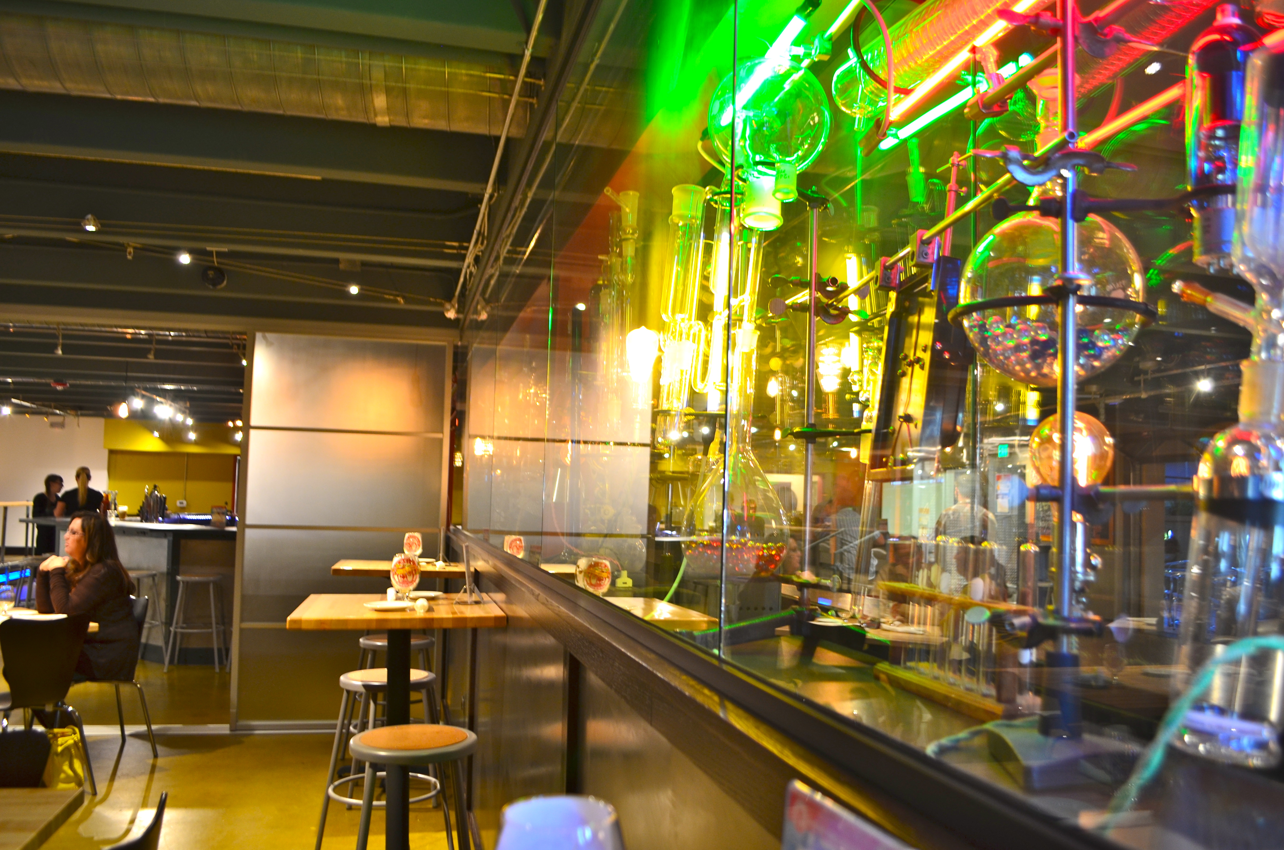 Glass garage doors restaurant -  The Spacious Restaurant Which Is Located In A Walk In Basement Style Space Decorated With Beakers Science Experimental Displays And Glass Garage Doors